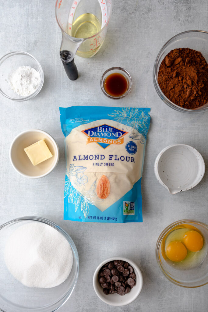 ingredients for almond flour brownies laid out in indivudal bowls on a grey surface
