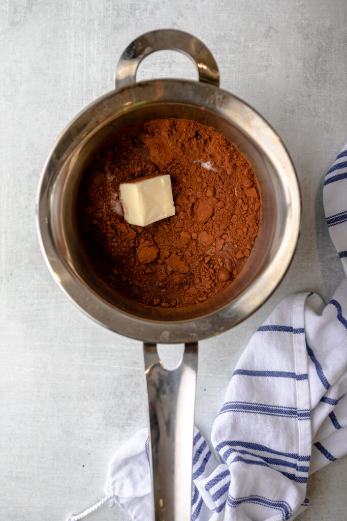 metal pot with cocoa powder, sugar, butter, and water sitting on a grey surface with a white and blue linen