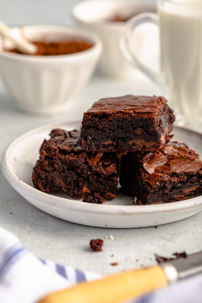 plate full of almond flour brownies on a grey surface with a glass of milk and bowls of chocolate in the background