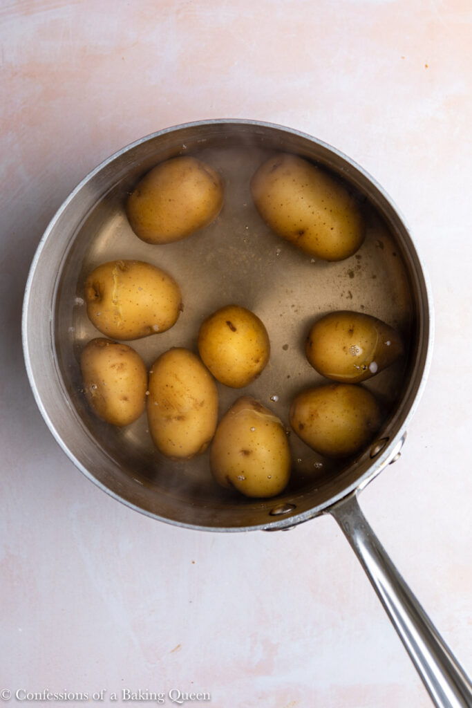 potatoes in a metal pot under water on a pink surface