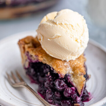 slice of blueberry pie with ice cream on top of a white plate with a fork on a grey surface