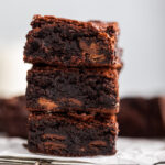 stack of almond flour brownies on a wire rack on a grey surface