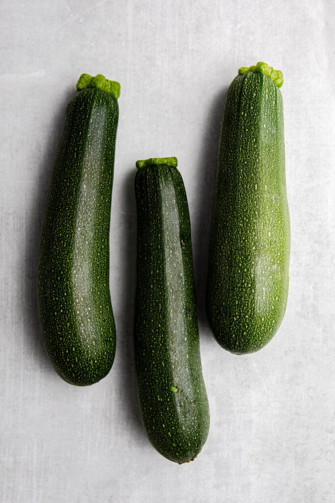 three zucchinis on a grey surface
