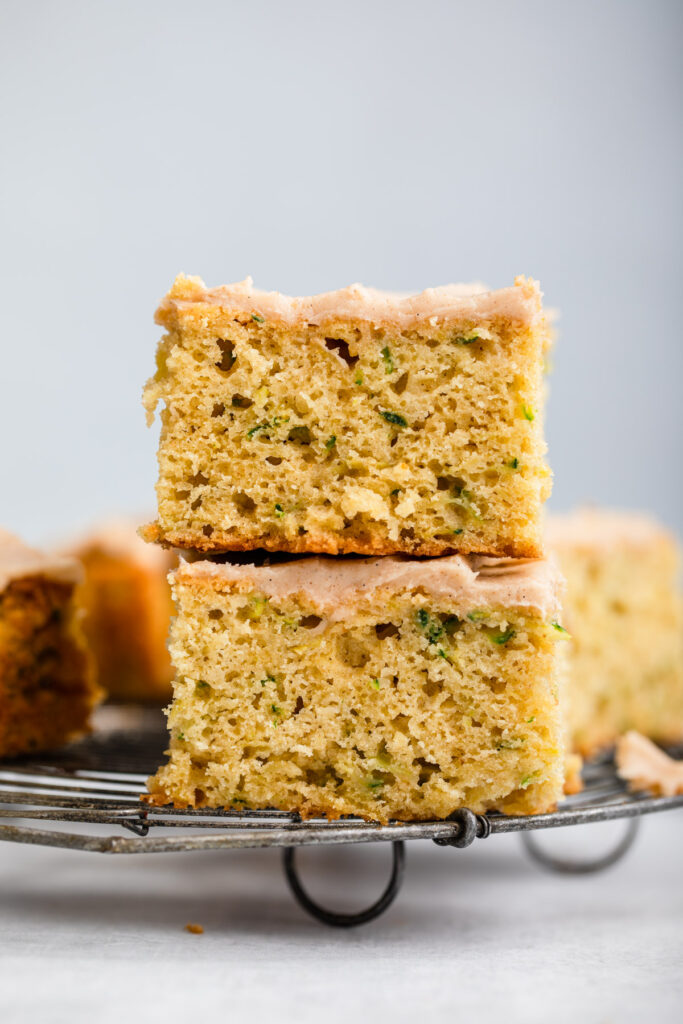 two pieces of zucchini snack cake stacked on top of each other on a wire rack on a grey surface