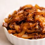 up close of a caramelized onions piled high in a white bowl on a grey surface (
