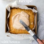hand holding an angled spatula spreading brown butter glaze on top of zucchini cake on a grey surface