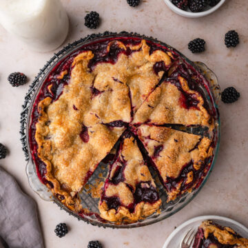 blackberry pie cut into slices on a light brown surface with a grey linen, slice of pie on a plate, bowl of blackberries and milk carafe