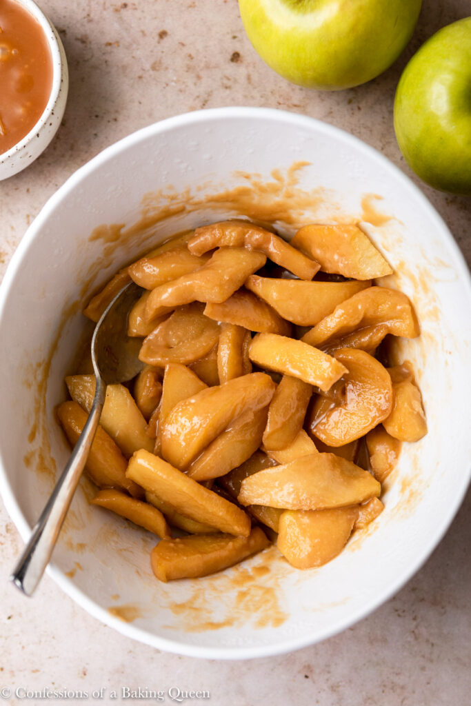 caramel apple slices in a white bowl on a light brown surface with apples and a bowl of caramel