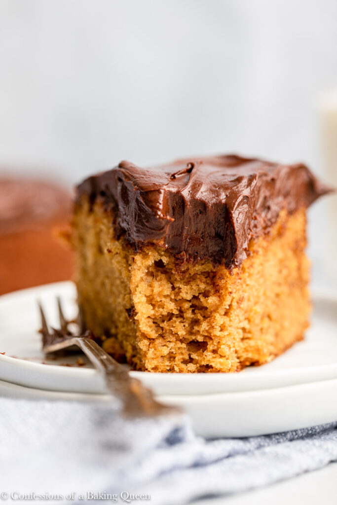 chocolate frosting on a slice of peanut bubtter cake on a white plate with a metal fork
