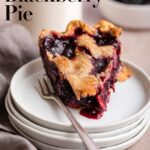 slice of blackberry pie on top of a stack of platees with a fork on a light brown surface with a grey linen