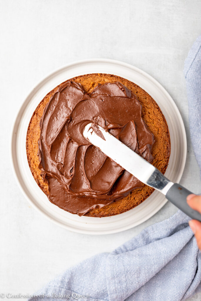 hand holding an angled spatula spreading chocolate frosting on top of peanut butter cake on a white plate on a light grey surface with a blue linen