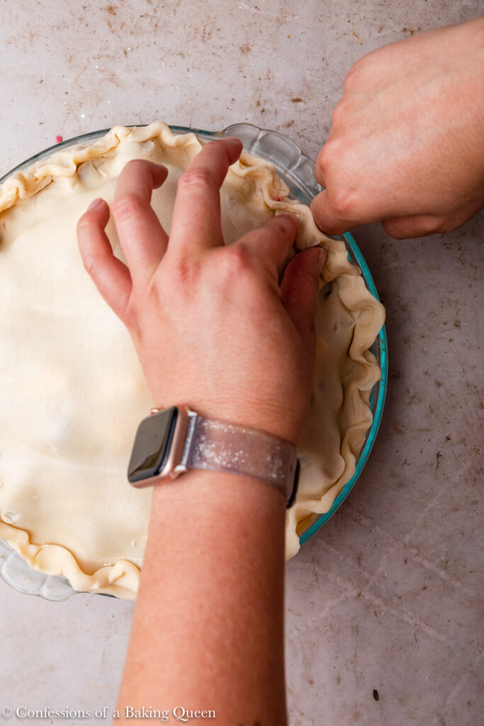 hands pinching pie crust together