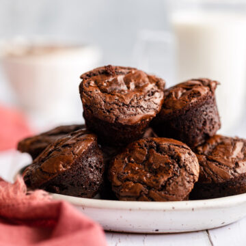 homemade brownie bites on a white plate on a white surface with a pink linen and glass of milk in the background