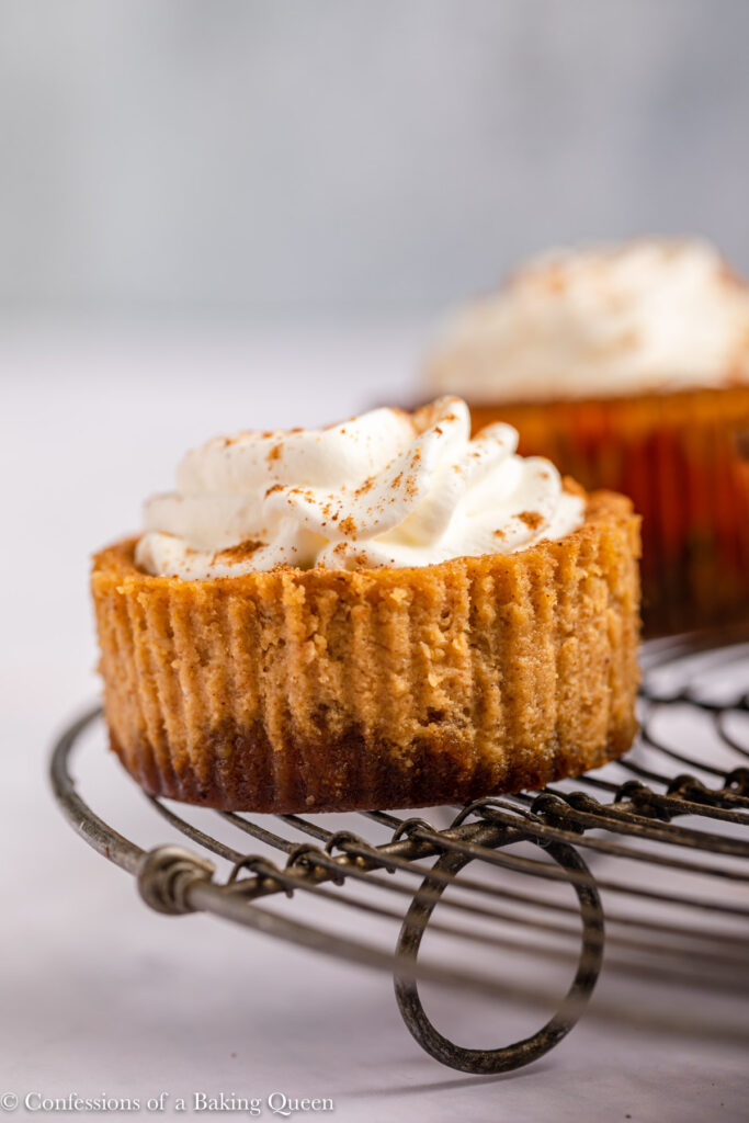 mini pumpkin cheesecake on a wire rack on a white surface
