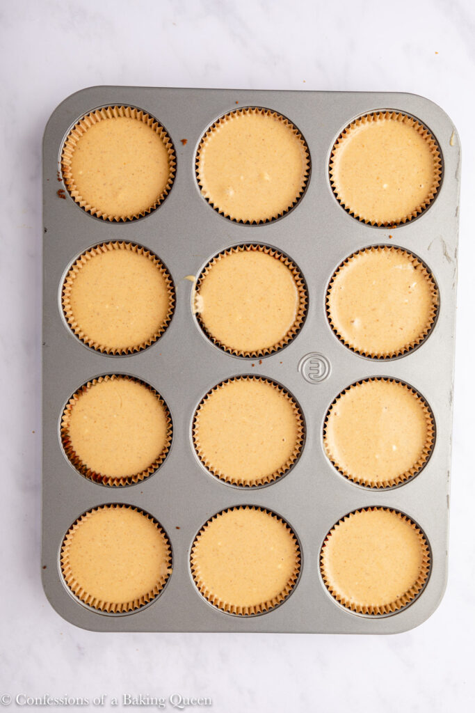 mini pumpkin cheesecakes in a cupcake pan before baking