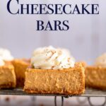 pumpkin cheesecake bars with whipped cream on a wire rack on a brown surface