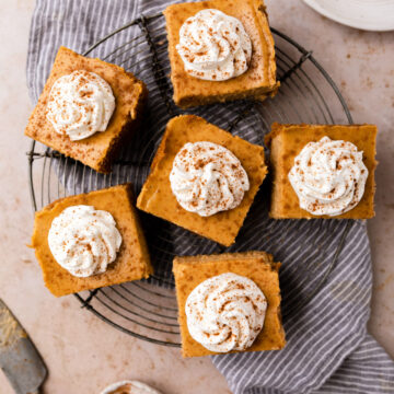 pumpkin cheesecake bars on a wire rack on top of a blue linen on a brown surface with a knife and small bowl of ground cinnamon