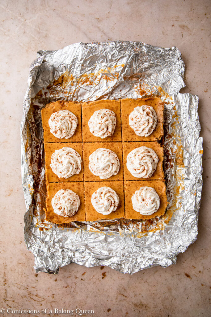 pumpkin cheesecake bars sliced and topped with whipped cream and pumpkin pie spice (1 of 1)
