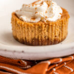 pumpkin cheesecake on a white plate on top of an orange linen