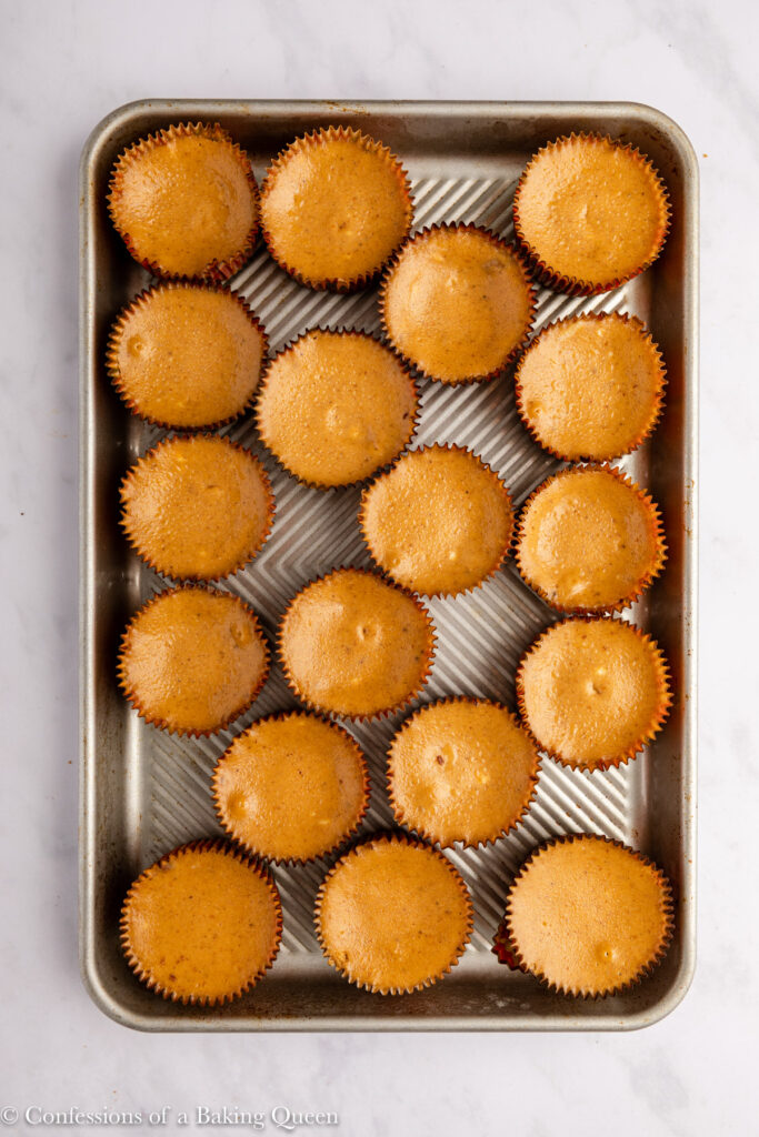 pumpkin cheesecakes on a baking sheet on a white marble surface