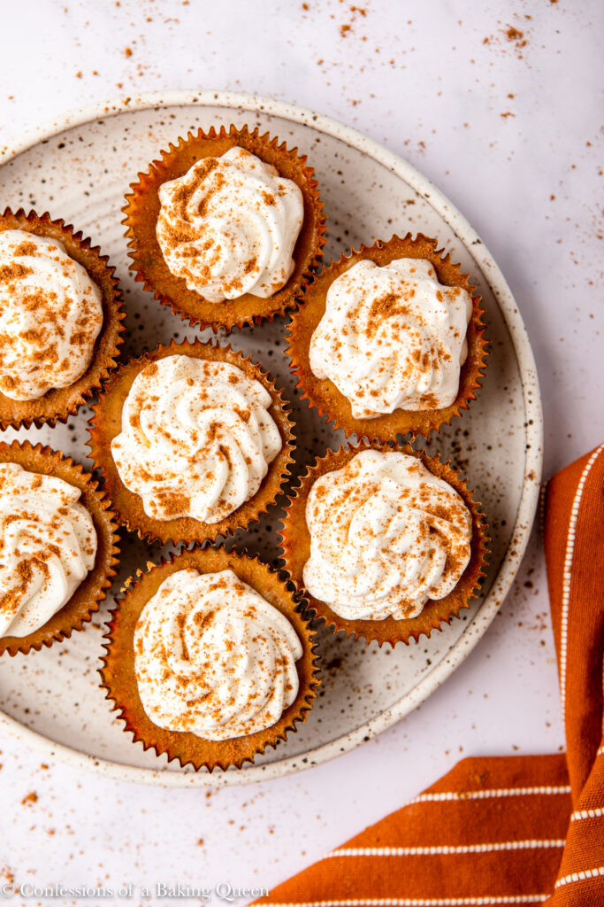 pumpkin cheesecakes on a white and brown speckled plate on a white surface with an orange linen