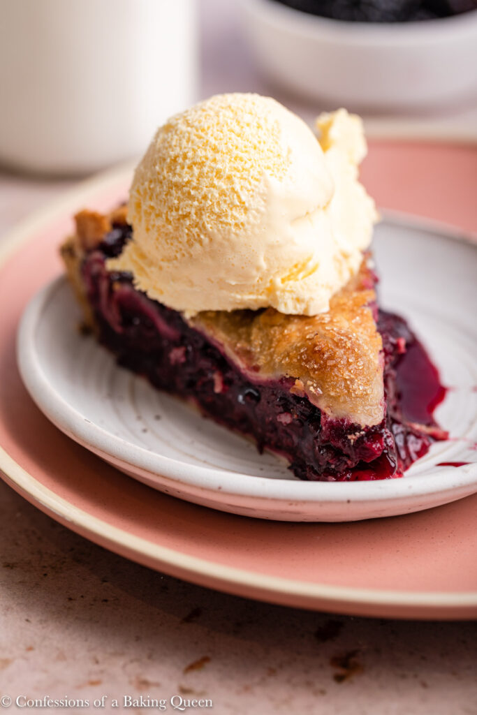 slice of blackberry pie a la mode on a white plate on a pink plate on a light brown surface