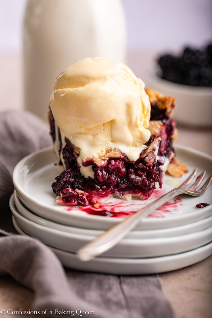 slice of blackberry pie with ice cream half eaten on a stack of white plates with a fork and grey linen on a brown linen