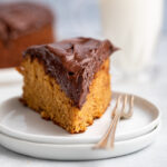 slice of peanut butter cake on a stack of white plate on a grey surface with more cake and a glass of milk in the background
