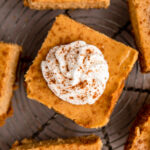 up close of pumpkin cheesecake bars on a wire rack on a brown surface