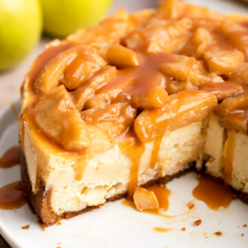 view of sliced open caramel apple cheesecake on a white plate with caramel dripping with apples in the background