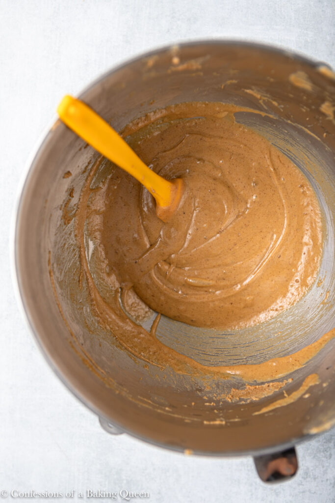 wet ingredients for a peanut butter cake in a metal mixing bowl with a yellow spatula on top of a grey surface