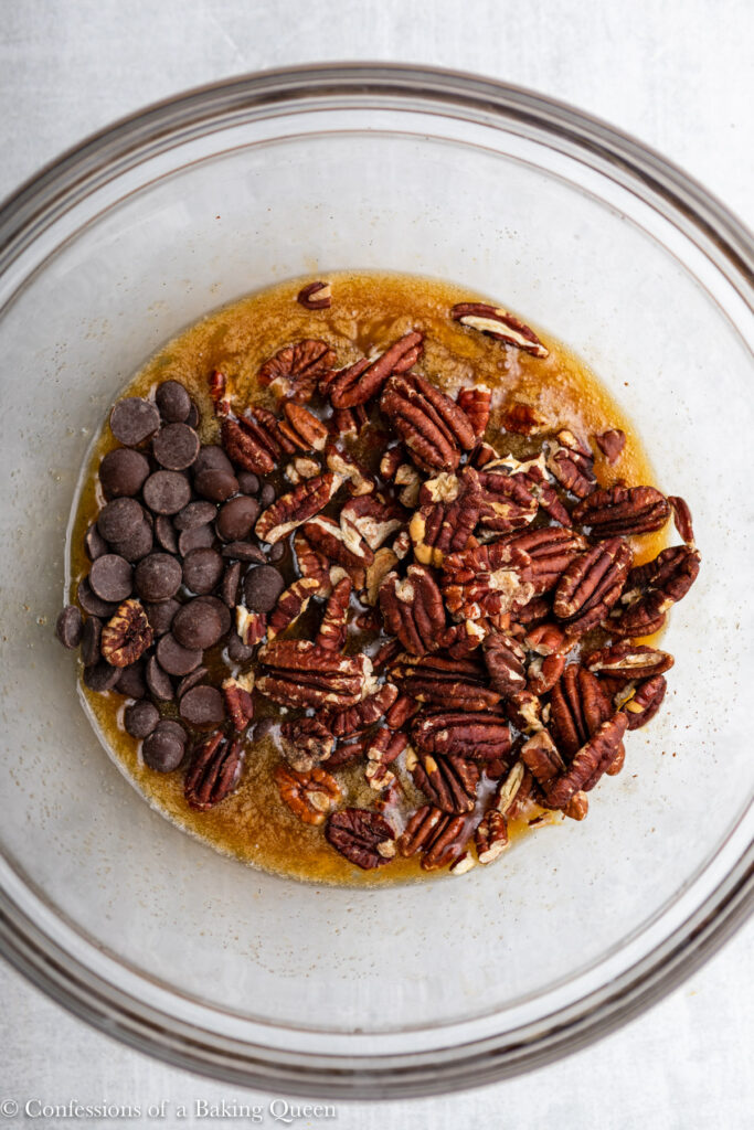 chocolate chips and pecans added to liquid ingredients in a glass bowl on a light grey surface