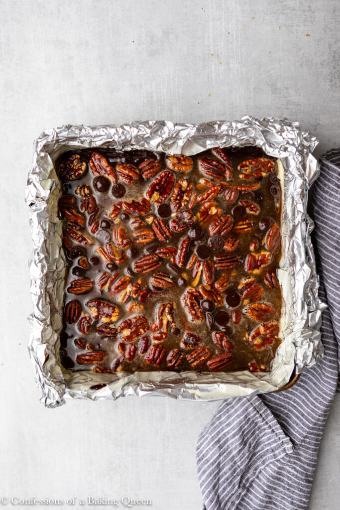 pecan pie brownies in a foil lined pan before baking sitting on a light grey surface with a navy blue and white linen