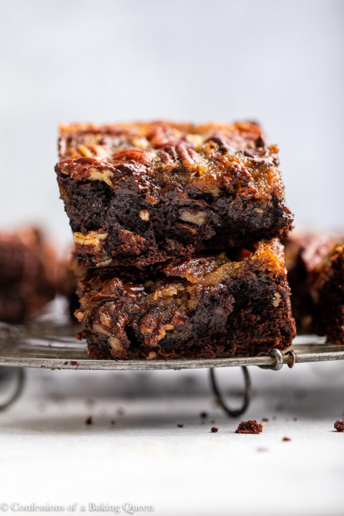 pecan pie brownies stacked on top of each other on a wire rack on a grey surface