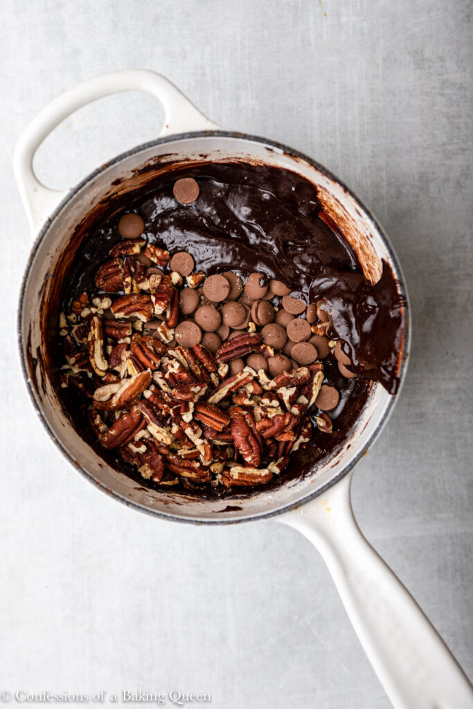 pecans and chocolate chips added to brownie batter in a white pot on a light grey surface (