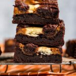 stack of pumpkin cream cheese brownies on a wire rack on top of an orange linen on a light grey surface
