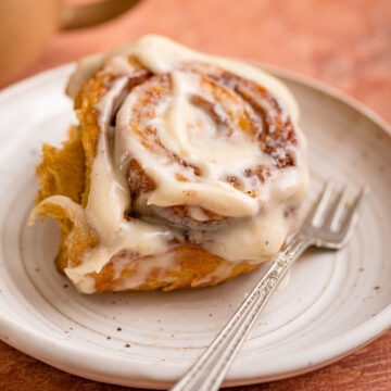 pumpkin cinnamon roll on a white plate with a fork and a cup of coffee in the background on a reddish brown surface