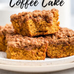 slices of pumpkin coffee cake stacked on top of each other on a white plate on a light grey surface