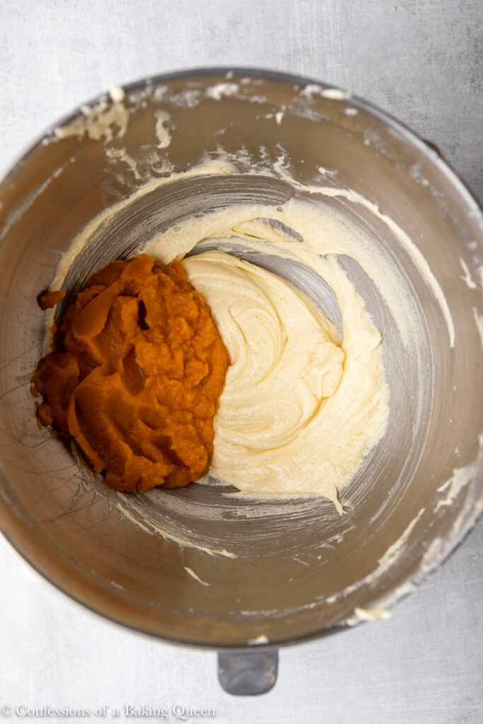 pumpkin puree and yogurt added to wet ingredients in a metal bowl for a pumpkin coffee cake recipe