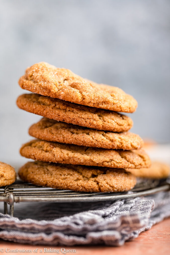 stack of pumpkin snickerdoodles on a wire rack on top of a blue linen on a reddish brown surface