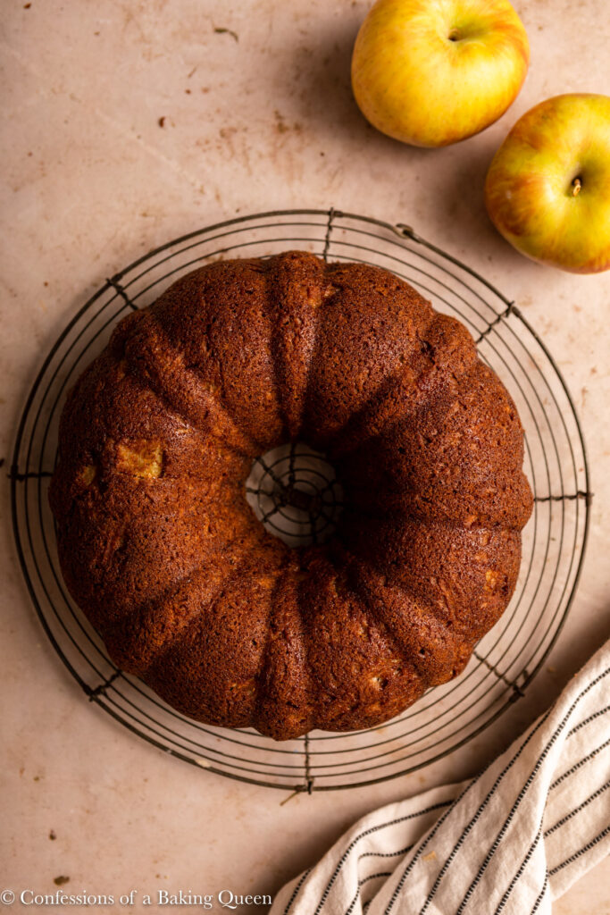 apple bundt cake cooling down on a wire rack on a light brown surface with a stripped white linen and apples