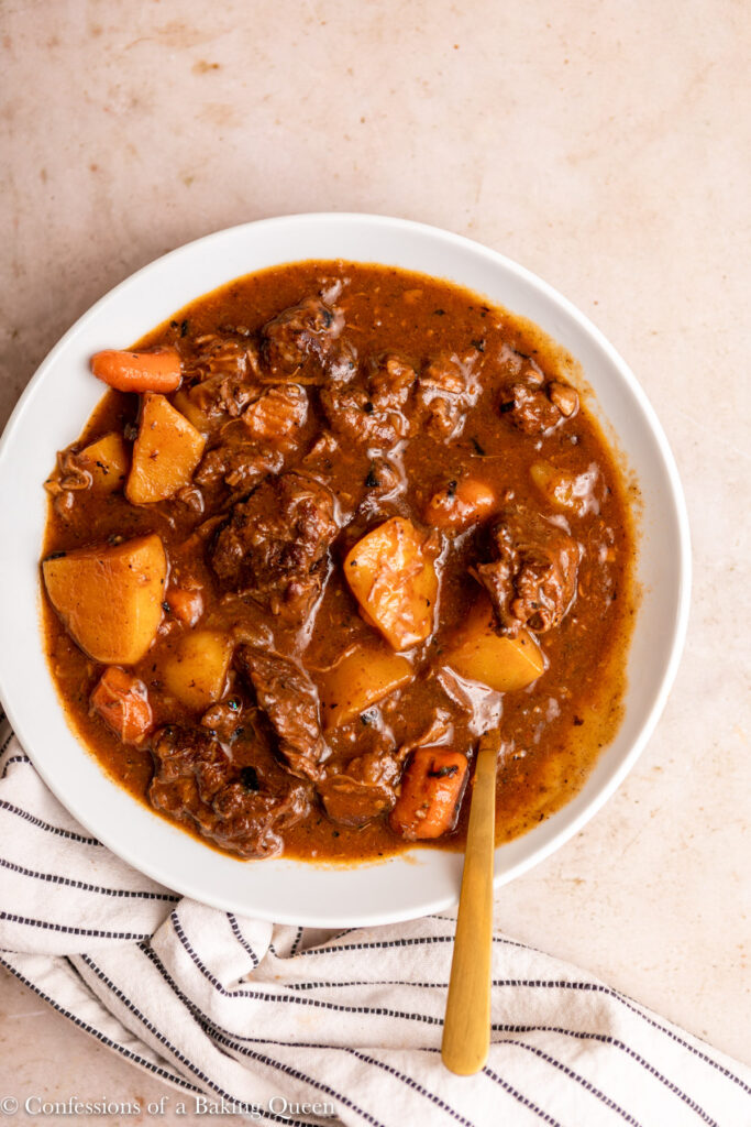 beef stew in a bowl with a spoon next to a white stripped linen on a light brown surface