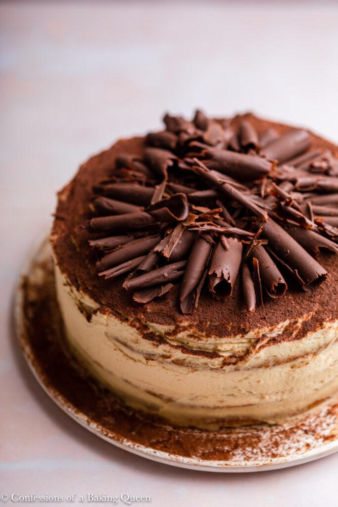 chocolate curls on top of a tiramisu cake on a light pink surface