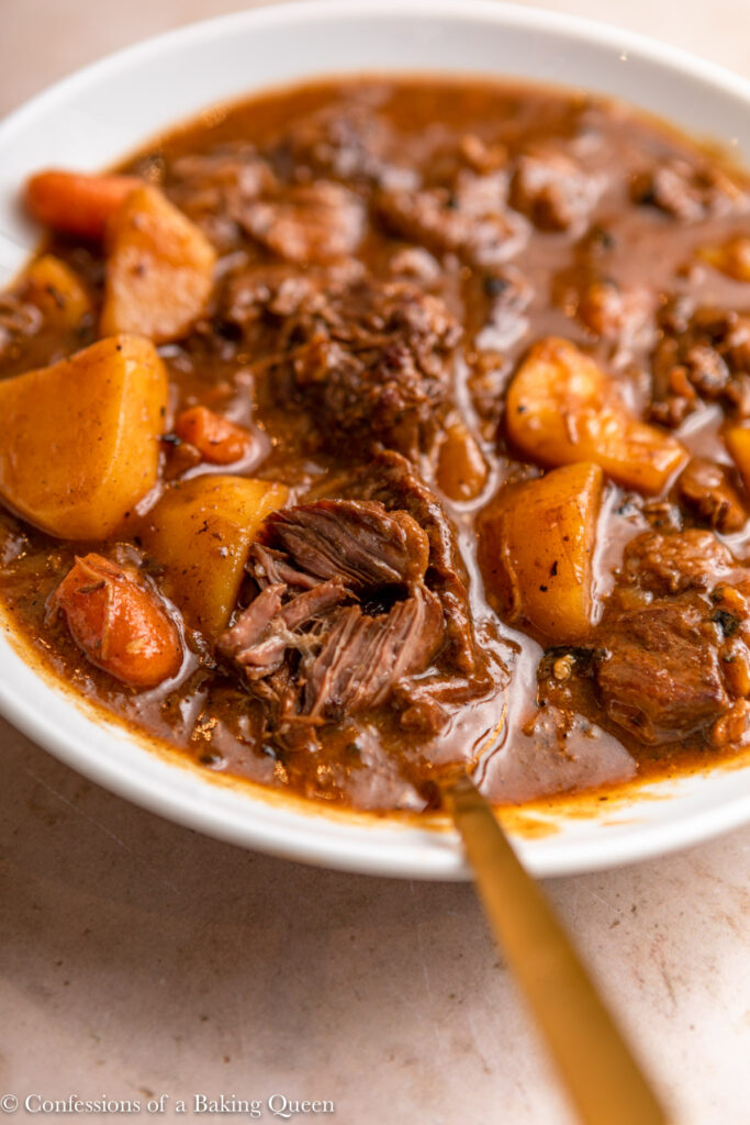 close up of beef stew in a white bowl with a gold spoon on a light brown surface