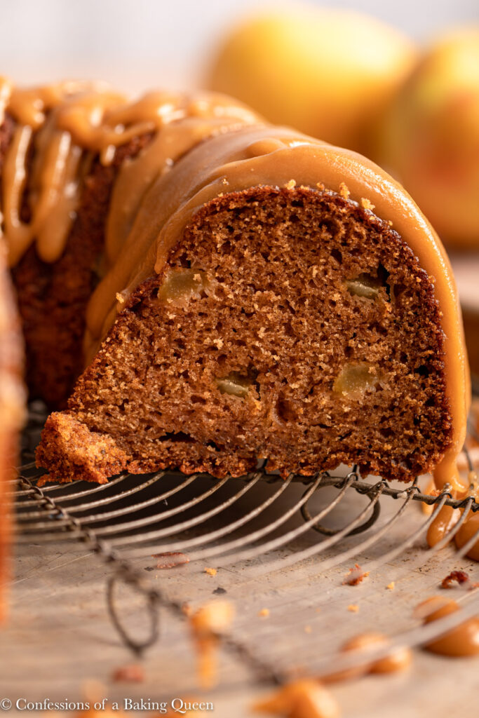 cut open apple bundt cake with caramel frosting on a wire rack on top of a sheet pan