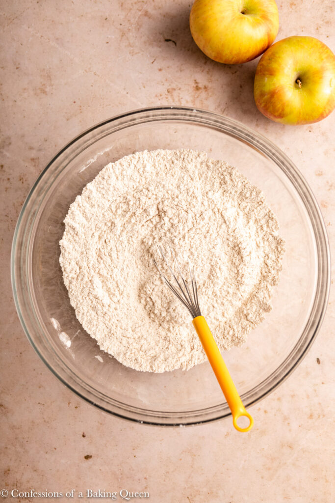 dry ingredients whisked together for apple cake in a glass bowl with a metal whisk on a light brown surface with a stripped white linen and apples