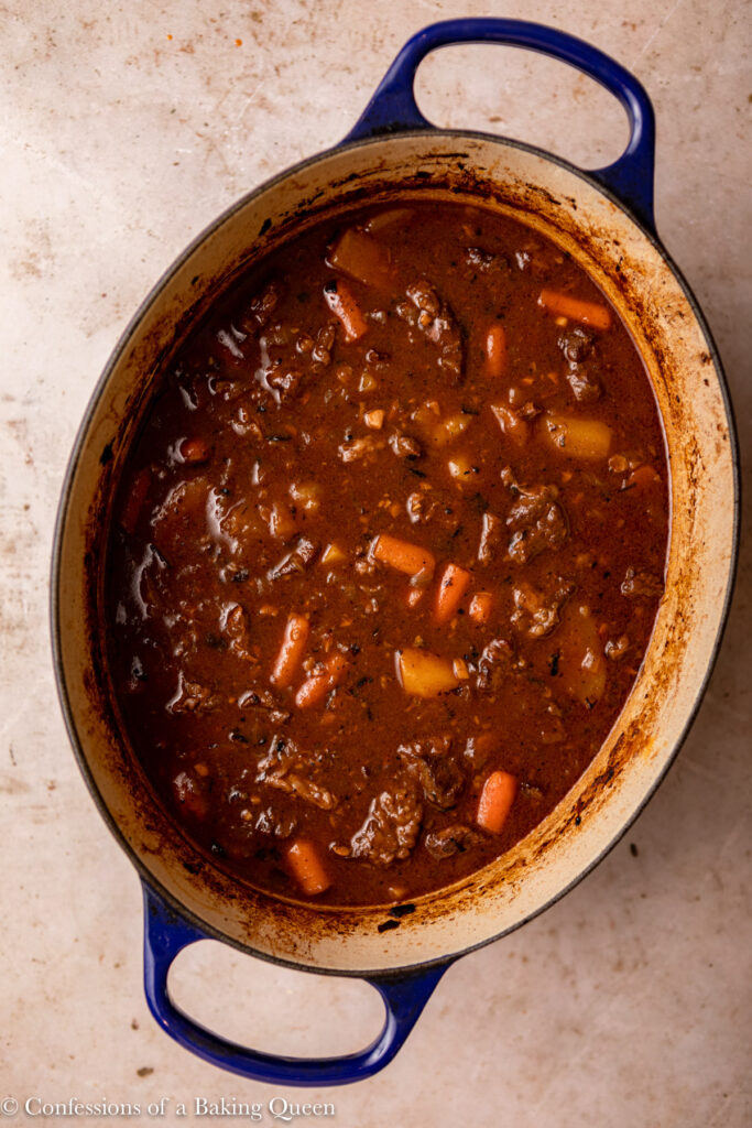 dutch oven beef stew in pot on a light brown surface