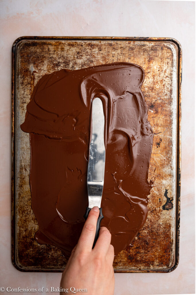 hand holding an angled spatula spreading melted chocolate on top of a baking sheet on a light pink surface