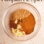 pumpkin pie spices in a glass bowl on a light brown surface
