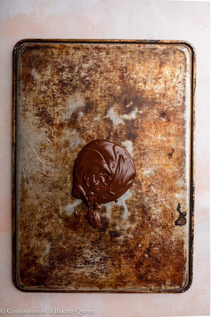 melted chocolate poured onto the back of a baking sheet sitting on a light pink surface